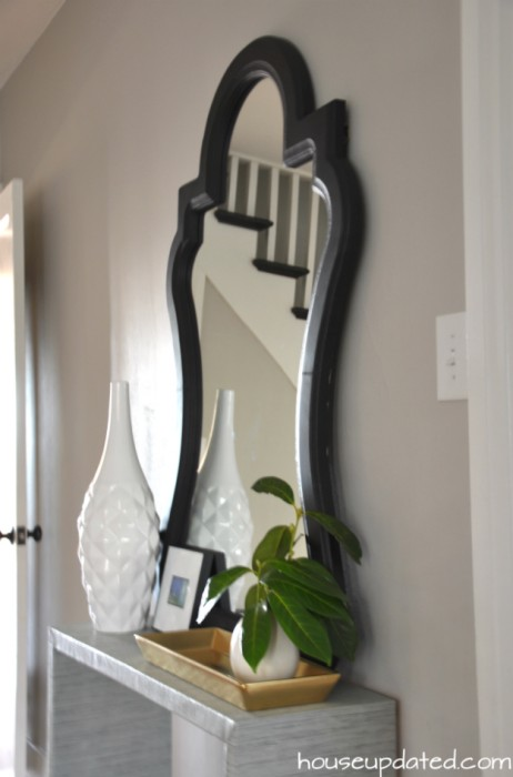 curvy entry mirror on console table