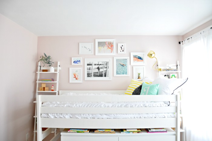 white bed pink turquoise gallery wall