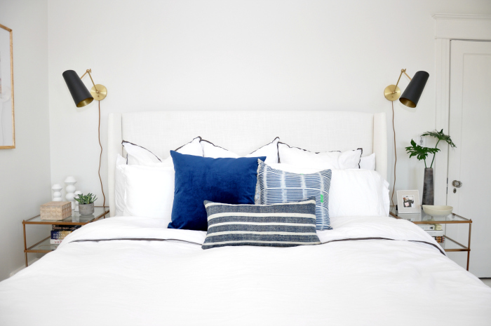 white-bed-black-sconces-blue-pillows